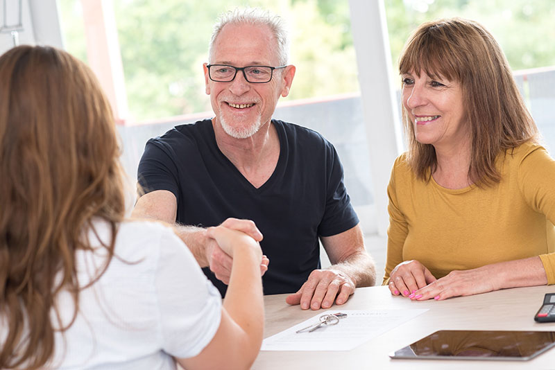 Senior couple shaking hands with real estate agent