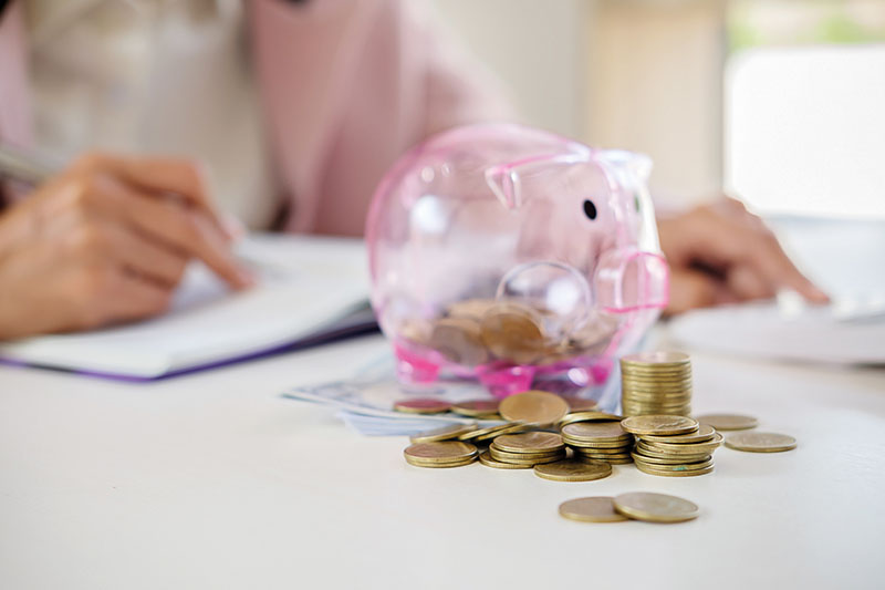 Business people sheltering coins and piggy bank at desk. saving concept